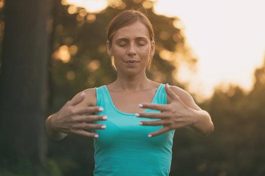 Beautiful woman enjoys exercising Tai Chi  in the nature.
