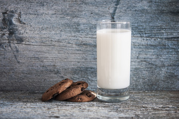 Chocolate chip cookies, milk, rustic wood background