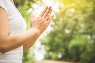 woman hands praying and do meditate peaceful at green park in the morning