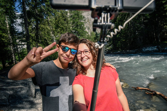 Couple of friends taking self portrait with selfie stick with a mountain river in background. Two young brothers make selfie on a phone outside in the park. Teens taking a self picture with smartphone