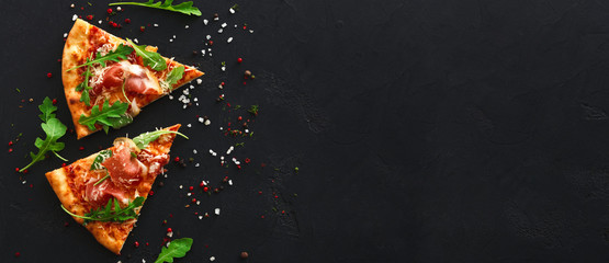 Slices of pizza with spices on black background