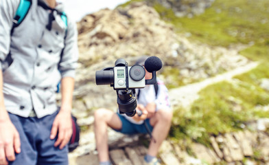 Blogger holding camera on monopod in mountains