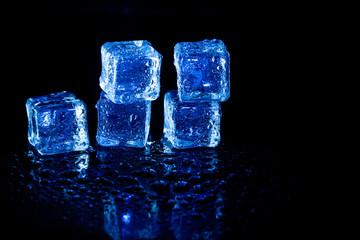 Fototapeta Blue ice cubes reflection on black table background.