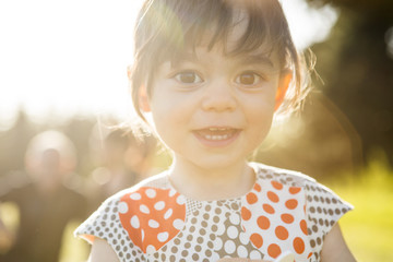 Cute portrait of a little girl in a dress playing in the grass at sunset.