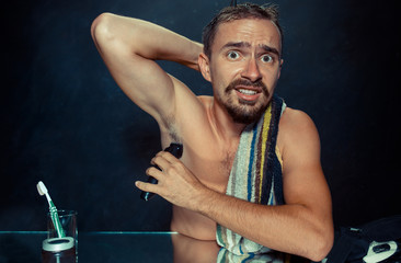 Photo of handsome man shaving his armpit. The young man in bedroom sitting in front of the mirror at home. Human skin and lifestyle concept