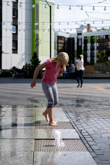life of children in a modern city - little girl having fun with fountains