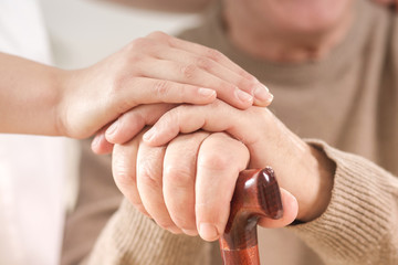 Close-up on senior person hand on walking stick and helpful caregiver