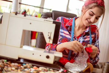 Young seamstress woman using sewing machine to design clothes