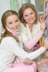 Close-up portrait of a mother and daughter drawing