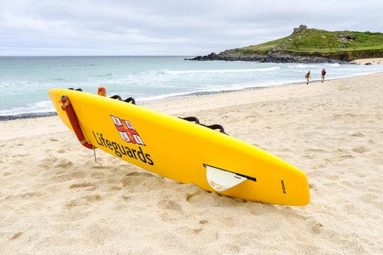 RNLI Lifeguards yellow surfboard on Porthmeor beach, Cornwall.