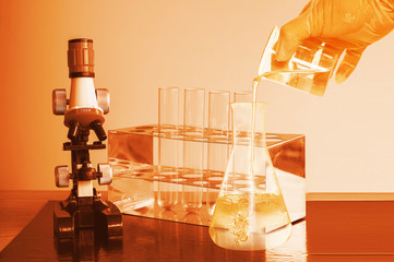 microscope and laboratory test tube on light blue background , science research equipment concept.