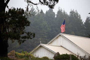 American flag flies atop white barn in forested area
