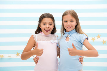 high quality. little girls show thumbs ups as symbol of high quality. success. little girls are best friends.