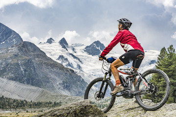 active senior woman, riding her e-mountain bike in the Roseg valley below the glaciers and summits of the Sella Group and Piz Roseg Wall mural