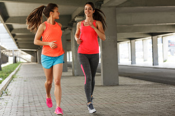 Two female runners jogging around the city.Urban workout concept.