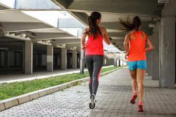 Two female runners jogging around the city.Urban workout concept.Rear view.