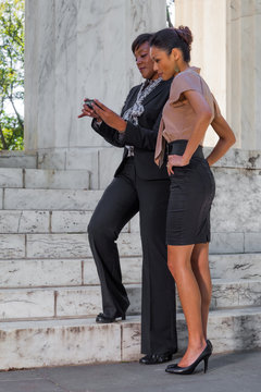 Two Business Women Looking at a Mobile Phone Outdoors, Next to Marble Steps