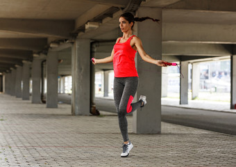 Female in sports outfit workout on the street with jump rope.