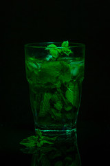 Glass of fresh mint tea on a dark background. Light painting. Copy space.