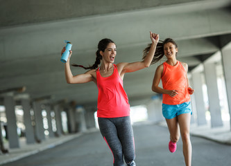 Two female friends jogging and racing through city parking lot.Celebrating win.