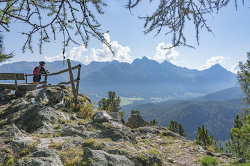 senior woman, taking a break from her Mountainbike trip and looking over the valley of upper Engadin above Celerina and Saint Moritz, Graubuenden, Switzerland