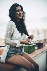 Young woman sitting at balcony and smiling