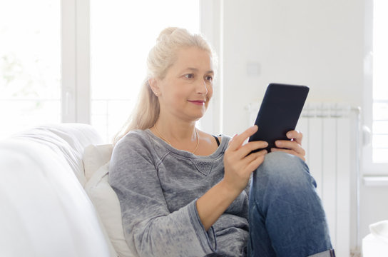 Woman with tablet in hands sitting on sofa