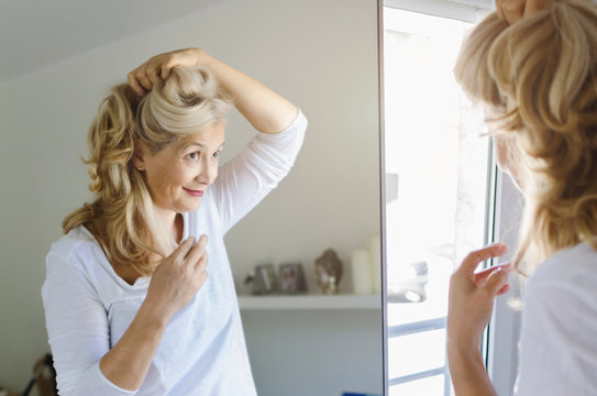 Woman cheking her hair in front of mirror