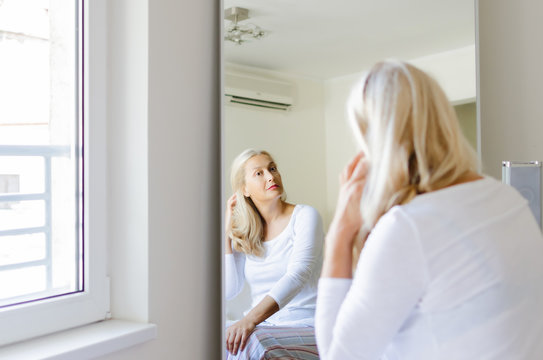 Senior woman sitting in front of mirror