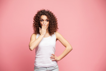 Portrait of amazed young woman over pink background.