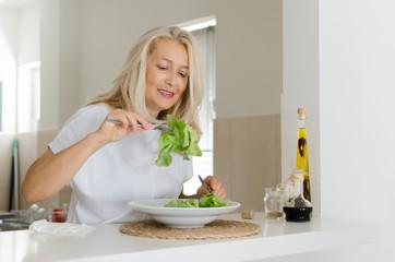 Senior woman eating green salad