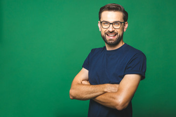 A portrait of young handsome man in casual isolated on green background with glasses.