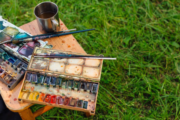 Palette of watercolor paints and brushes on the wooden background.