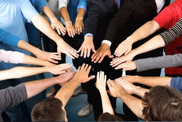 Close-up view of group of people stacking hands