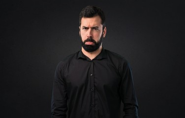 Sad handsome man with beard on black background