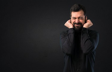 Handsome man with beard covering his ears on black background
