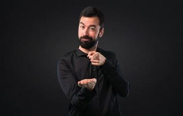 Handsome man with beard holding something on black background