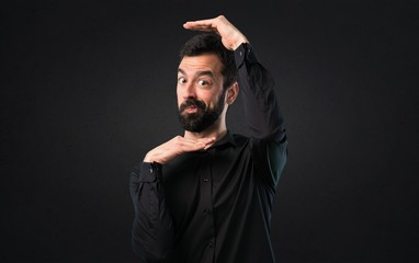 Handsome man with beard focusing his face on black background
