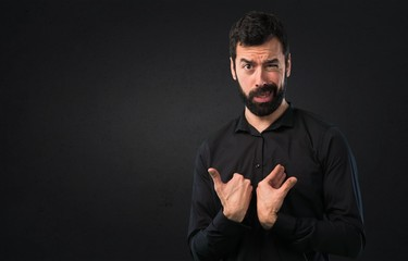 Handsome man with beard making surprise gesture on black background