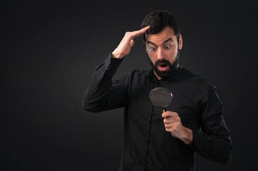 Handsome man with beard with magnifying glass on black background