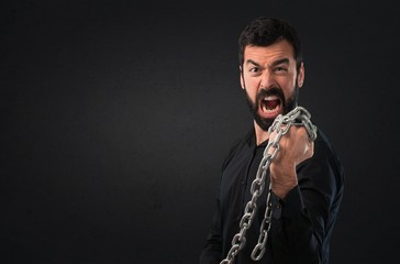 Handsome man with beard with chains on black background