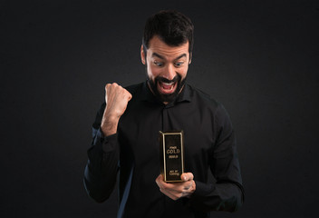 Handsome man with beard with gold ingot on black background