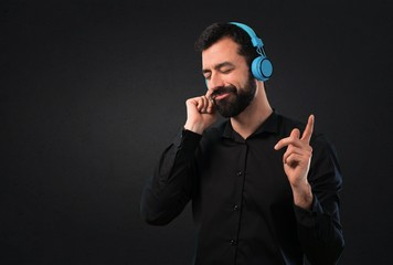 Handsome man with beard listening music on black background