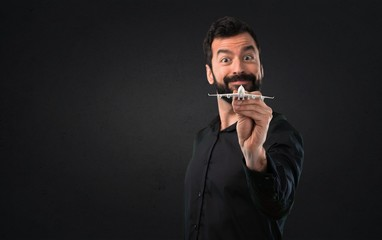 Handsome man with beard holding a toy airplane on black background
