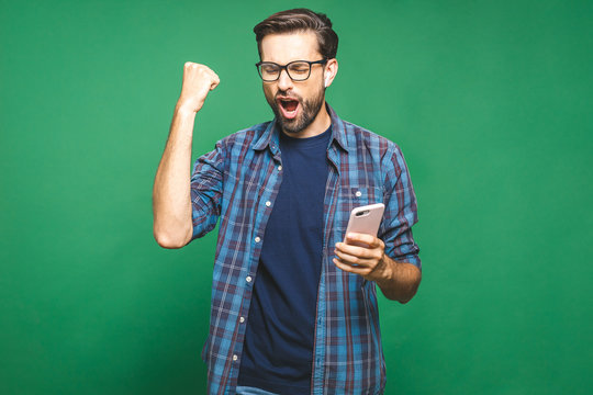 I'm a winner! Happy man holding smartphone and celebrating his success over green background.