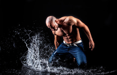 very muscular handsome athletic man striking with a hand on water
