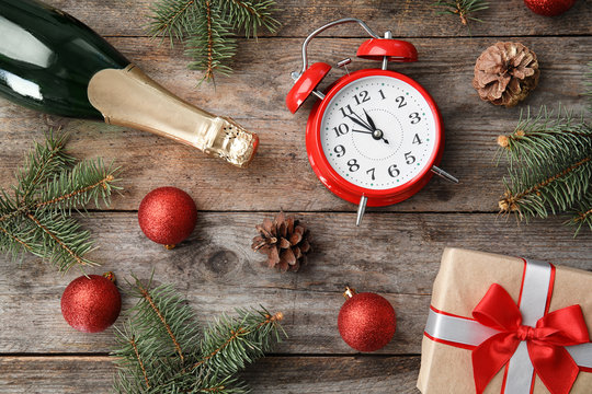 Christmas composition with bottle of champagne and alarm clock on wooden background, top view