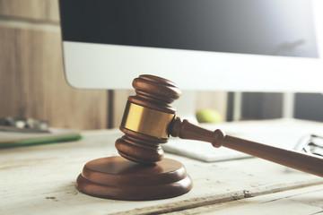 Wooden judge hammer on laptop computer