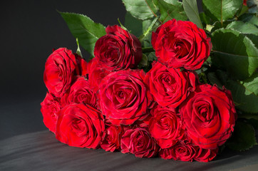 Bright bouquet of red roses on a black background