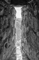 Ventana de piedra con vistas a un paisaje de montaña